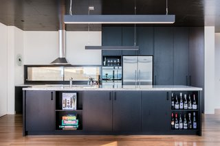 A granite island countertop and black American oak cabinetry are a winning combination for the utilitarian kitchen. The sleek kitchen pendant lights are Matric-P4's from Lightnet.