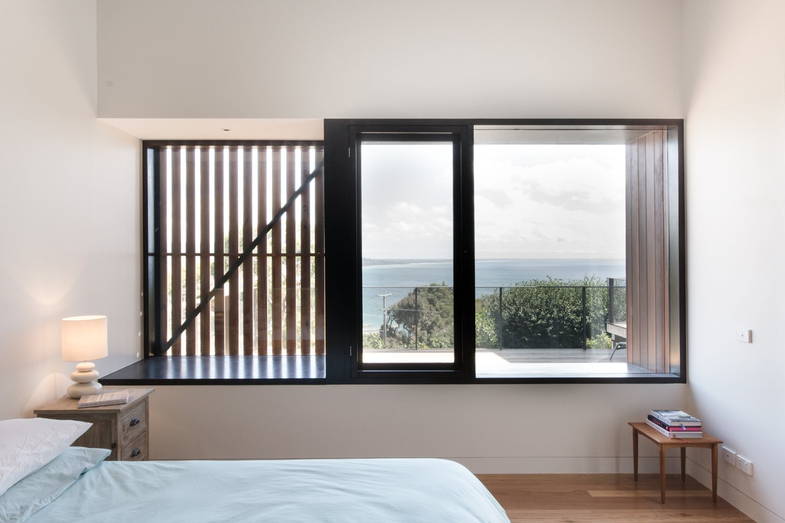 """External shutters and screens allow the homeowners to manage the sunlight and cross ventilation in certain rooms. Manos Mavridis, also of OLA Studio, explains, """"There was a preference for the screens to be manually operated to minimize ongoing maintenance costs and encourage user engagement with their environment."""" Tagged: Bedroom, Bed, Lamps, Table Lighting, Night Stands, and Medium Hardwood Floor.  Photo 8 of 8 in An Australian Beach Home with Stunning Ocean Views from Martha"""