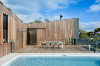 To reduce the home's environmental footprint, OLA installed rain water collection tanks and solar panels, which the house relies upon for water and electricity. White tile and tan travertine pool pavers mimic the color palette of the nearby beach.