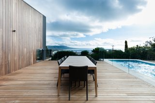 A Mood Outdoor Table by Studio Segers for Tribù is surrounded by Terra Outdoor Chairs by Bram Bollen, also for Tribù. They rest atop silvertop ash hardwood decking.