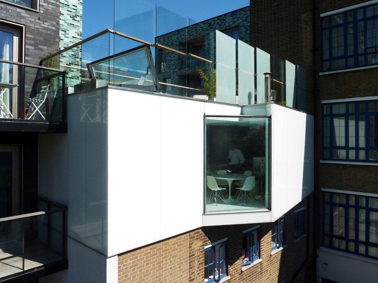 The expansion is lightweight timber construction clad in glass with a stainless steel trim, producing a glossy, reflective veneer. The full-height structural glass wraps overhead to capture more light. The roof terrace, with a balustrade and partial privacy screening, is accessible by a hydraulic roof hatch.  Photo 1 of 7 in A Tiny Live/Work Addition Crowns a Historic London House