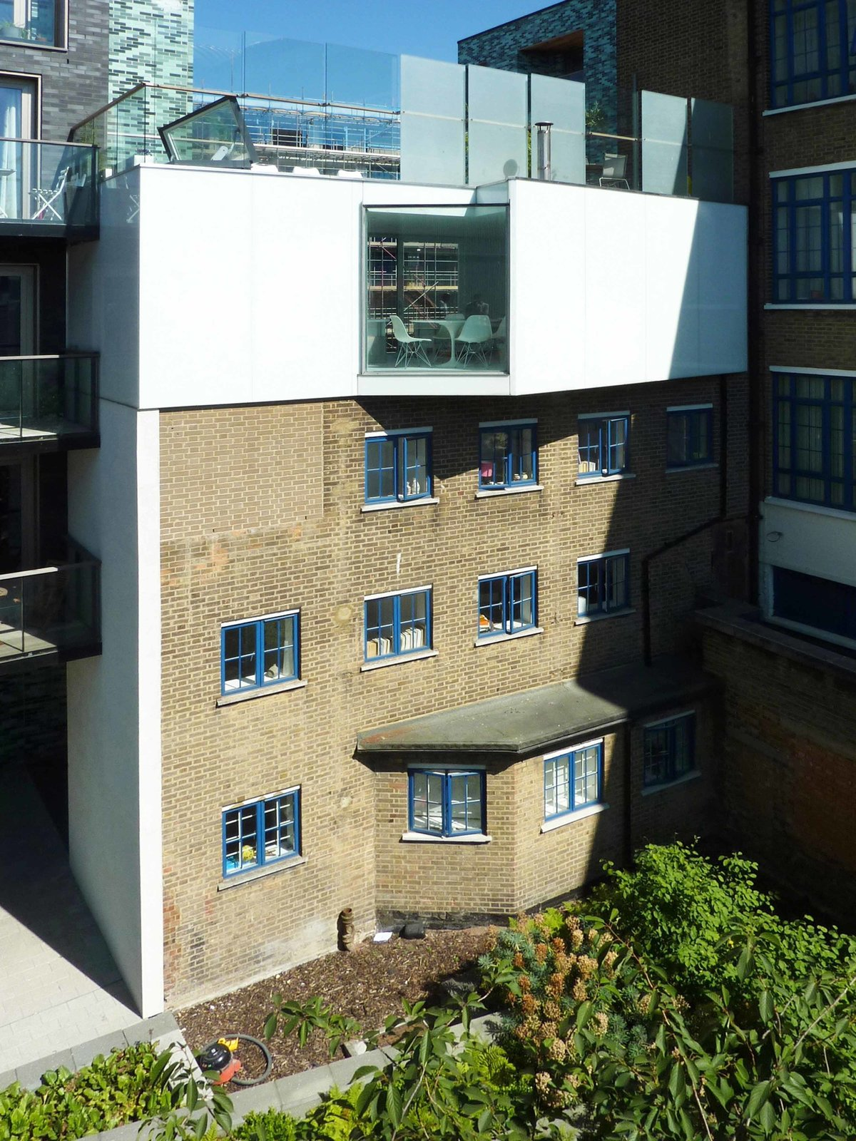 A stepped back view shows the confined site, bracketed by multi-unit residential buildings. The lone window is angled to grab maximum light while protecting privacy.  Photo 2 of 7 in A Tiny Live/Work Addition Crowns a Historic London House