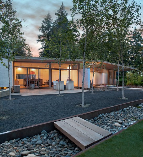 """They wanted the new cabin to make a 'L' shape with the older cabin, but I convinced them to mimic the old cabin on the opposite side,"" architect D'Arcy Jones says. ""So the new site has two buildings across from each other, like an equal sign."" Birch trees grow between the cabins in a shared courtyard.  Photo 2 of 10 in A Couple's Cherished Vacation Home is Given a Second Life"