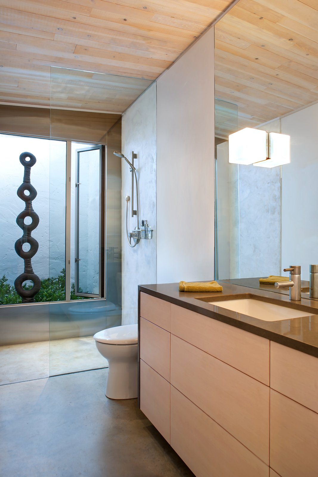 A Toto toilet and bathroom sink, with a faucet by GROHE, are illuminated by a Leucos light fixture. Birgit Piskor designed the sculpture in the garden beside the shower. Tagged: Bath Room, Enclosed Shower, Full Shower, and Concrete Floor.  Photo 7 of 10 in A Couple's Cherished Vacation Home is Given a Second Life