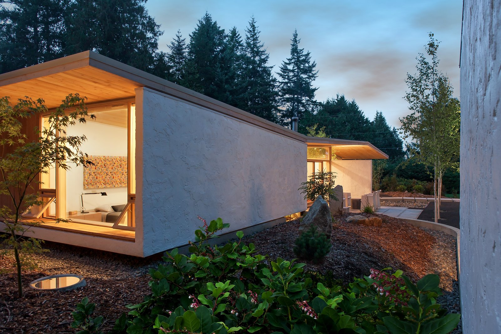 """""""[The house] avoids the mass or heaviness of too much timber construction, so with a few hidden steel beams, it seems to float and hover over the site in a delicate way,"""" Jones says. Salal, a native plant to the Pacific Northwest, and fern act as the site's groundcover.  Photo 8 of 10 in A Couple's Cherished Vacation Home is Given a Second Life"""