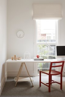 The study has a fun, playful atmosphere thanks to a red Square Dining Chair from MAP, a Tempo wall clock by Naoto Fukasawa for Magis, and house sculpture from David Band.