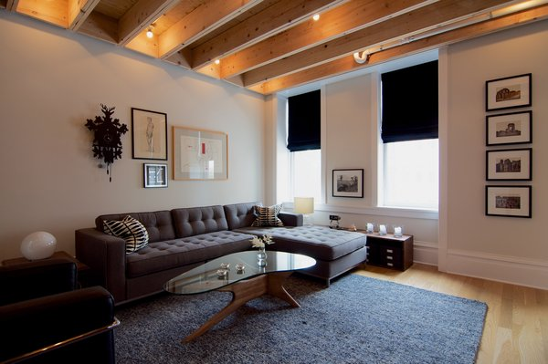 """""""It was a design priority that any modern interventions had an articulate edge or gap against the existing space,"""" says Shively. As a result, he designed a subtle gap between the exposed beam ceiling and the existing walls. The living room also features a Gus* Modern sofa and Adrian Pearsall coffee table."""