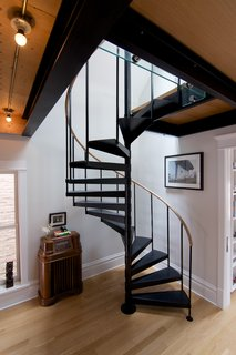 Shively had a carpenter from TomKal Construction build a custom handrail, out of white oak to match his floors, for this spiral staircase.