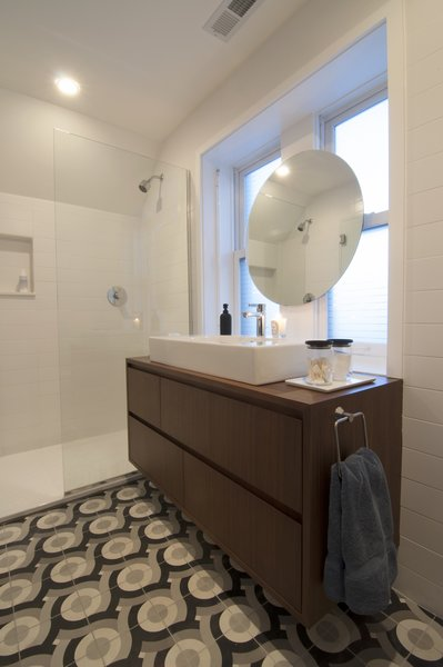 """Shively describes himself as """"big on graphics"""" and designed these tiles, produced by Original Mission Tile in San Luis, Mexico, to add his own flair to the master bathroom. A simple floating vanity and minimalist shower let the custom tilework take center stage."""