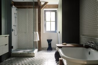 In the master bathroom, the cement floor tiles are by Mosaic House; the glazed subway tiles are from Daltile; and the trim is honed, vein-cut Montclair Danby marble. The Signature Hardware tub sits in a custom wood cradle designed to match the home's timber frame; the fixtures are by Waterworks. The Twist stool is from Classic Country in nearby Hudson, New York.