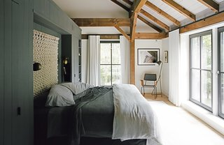"A Passive House and ""Sauna Tower"" Join a 19th-Century Barn in the Hudson Valley - Photo 4 of 13 - The bedding is intentionally simple, without layers of unnecessary pillows, and the ""non-headboard headboard,"" as Santos describes it, is a loose macramé wall hanging by Sally England. The built-in storage wall that defines the space is painted Kendall Charcoal by Benjamin Moore in a matte finish—a shade used on millwork throughout the house. The Isaac brass sconces are from Schoolhouse Electric, and the floor lamp is from Crate & Barrel. The rocker was custom made by Onefortythree in Las Vegas."