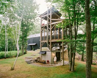 "A Passive House and ""Sauna Tower"" Join a 19th-Century Barn in the Hudson Valley - Photo 2 of 13 - Connected to the main house by a narrow bridge, a three-story cedar tower with a sauna at its base recalls a tree house. The screened-in second level includes a table and chairs for enjoying an outdoor meal, while a swing on the tower's top level provides a perch to take in the surrounding birch trees."