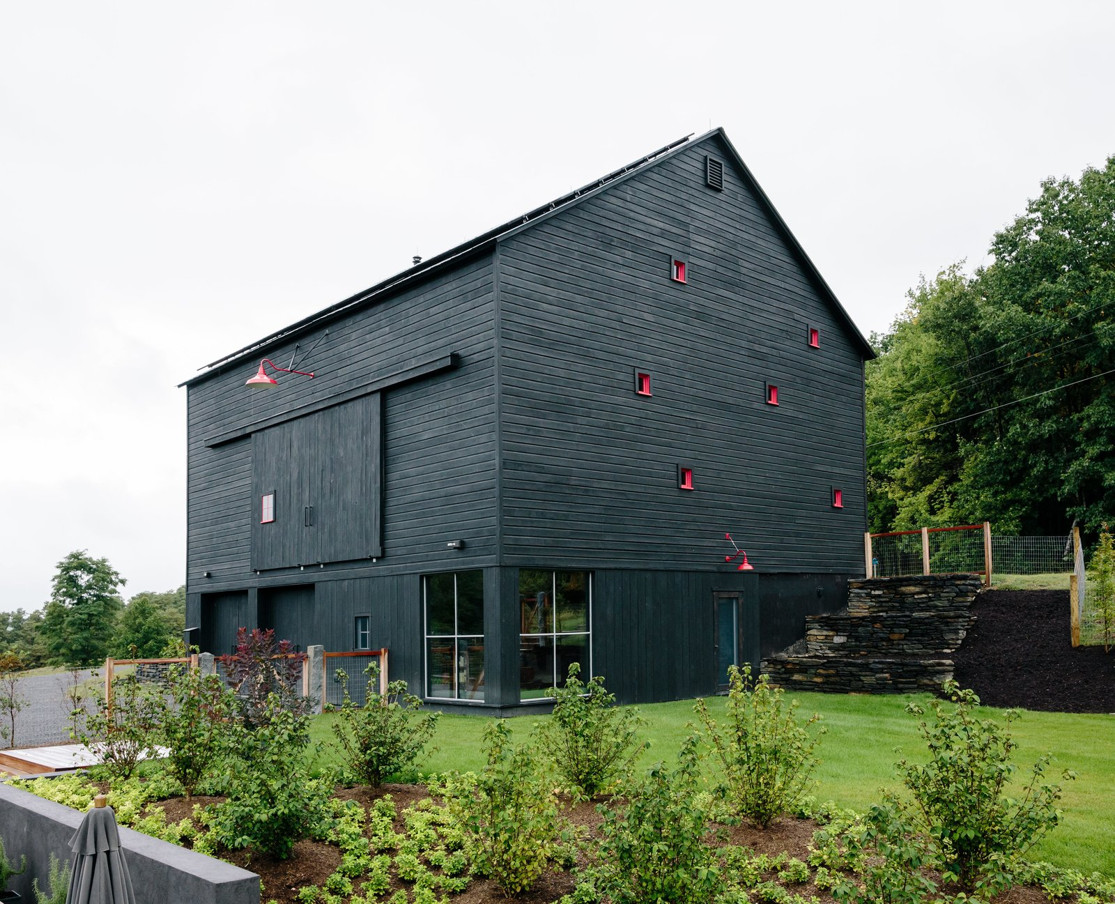 """Gardens, Grass, Exterior, Wood Siding Material, Barn Building Type, House Building Type, Gable RoofLine, Cabin Building Type, and Farmhouse Building Type While the house is a private sanctuary, the barn is a gathering place, especially in summer. On its lower level, a studio apartment recalls the main house with its Intus windows oriented to maximize solar gain.  Photo 10 of 11 in A Guide to Shou Sugi Ban and 8 Homes Featuring the Japanese Technique from A Passive House and """"Sauna Tower"""" Join a 19th-Century Barn in the Hudson Valley"""