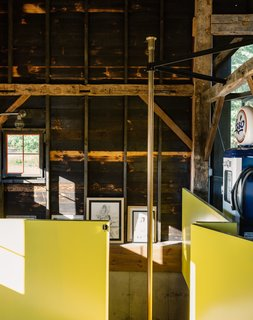 "A Passive House and ""Sauna Tower"" Join a 19th-Century Barn in the Hudson Valley - Photo 9 of 13 - The contractor sourced the brass pole from a fire station in Boston. The surrounding wall is painted in semi-gloss paint in Citrus by Sherwin Williams, a sunny hue the team playfully referred to as Dwell-ow."