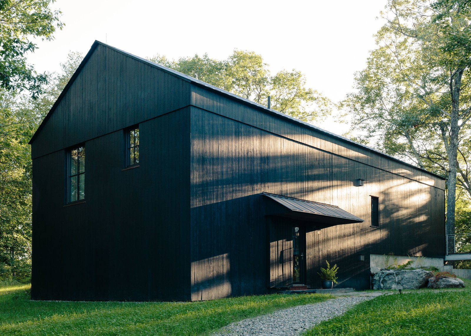 """Exterior, House Building Type, Gable RoofLine, and Wood Siding Material """"Who better than the farmer and the farmer's family to know how most effectively and easily to find efficiency?"""" says architect Alan Barlis. Regional architecture inspired the barn-life structure of the house, an open volume that aides in efficient heating and cooling of the space.  Photo 12 of 13 in A Passive House and """"Sauna Tower"""" Join a 19th-Century Barn in the Hudson Valley"""