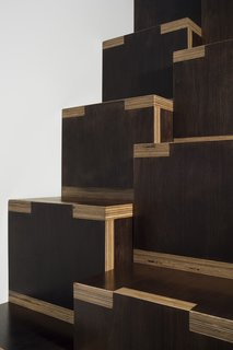 The interlocking, exposed edges of these plywood steps designed by General Assembly are both sculptural and functional, helping to visually orient climbers as they ascend with the pronounced contrast between the dark veneer of the plywood and the lighter exposed edges. The stairs were designed as a kit-of-parts to reduce cost, and also provide open storage on the side.
