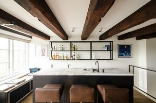 """Architecture and interior design firm Standard Studio renovated this home for their client, a young stockbroker, in a 1752 sugar refinery on the Bloemgracht canal in Amsterdam. One of the home's many stylish features is a wet bar that's connected to the kitchen by a flight of stairs, which is fully-equipped with cohesive, custom fittings and furniture by Eginstill. Each living area flows freely into the next, in an effort to """"make the space as open as possible, just like it used to be when it was a sugar refinery,"""" says van Hulzen. """"We wanted to [return] the building to its old glory."""""""