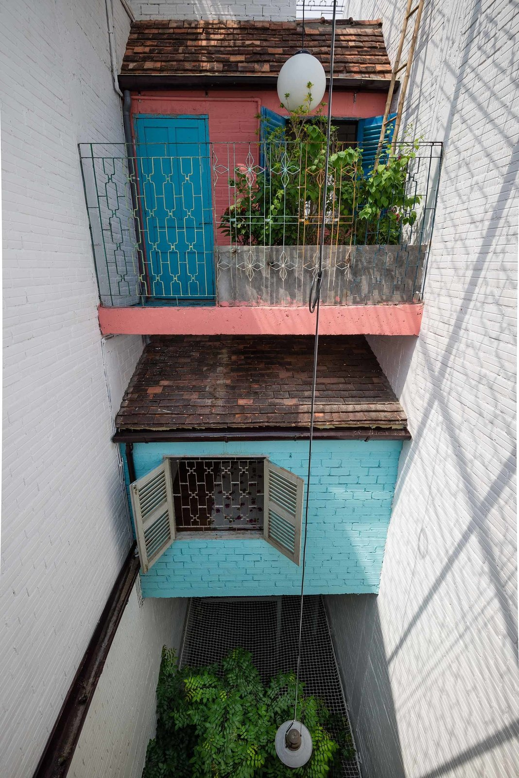 Flowering balconies are common in Saigon, where residents can interact with the city outside. Here, a beautifully patterned steel frame contains a cantilevered internal balcony, which looks out over the outdoor dining area's net ceiling.  Photo 9 of 10 in A Narrow Courtyard Joins a Unique Two-Family Home in Saigon