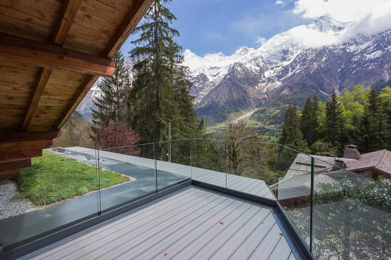 Glass walls fence in an outdoor deck without obstructing spectacular views of the mountains and valley. Tagged: Outdoor, Small Patio, Porch, Deck, and Wood Patio, Porch, Deck.  Photo 5 of 8 in A Mountain Hideaway Plants a Green Roof in the French Alps