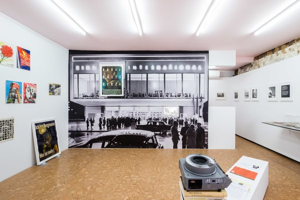 """""""This view captures the main installation gesture of the exhibition and also what's visible from street level. In his exhibition designs, Klaus Wittkugel often used large-scale panoramas of the city to transport the viewer into another context,"""" notes Krishnamurthy. """"Here, I'm turning this display strategy back onto Wittkugel himself. This is an image of Kino International, a modern film theater in East Berlin from 1963. For this architectural icon, Wittkugel designed the signage, including a clever spot to hang a poster as the 'space' in the name of the building. Here, I've blown up a historical image of the façade to room-sized proportions and gone one step further: one of Wittkugel's most striking posters, Das Kalte Herz [The Cold Heart], 1950, hangs framed on top of the building. An analogue slide projector plays a loop of selected images from Wittkugel's exhibition designs, retrospective exhibitions, and architectural commissions, interspersed with contemporary images of those same locations and screenshots of the digital models of my exhibition design that mirror these historical views. Installed as if the spectators out front are watching the projection, this display is the centerpiece of the show.""""  Photo 5 of 6 in A Look at Klaus Wittkugel, East Germany's Most Prolific Graphic Designer"""