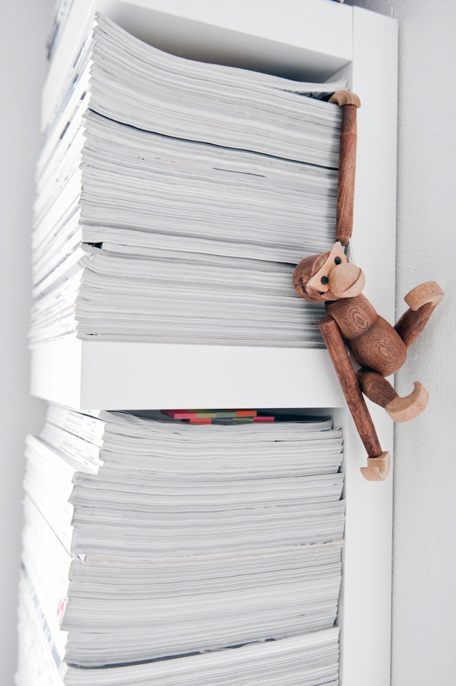 Even the family's old magazines are turned inward on the shelf to preserve the house's monochrome palette. Playful details, like this little monkey, add visual surprise.  Photo 5 of 10 in A Run-Down Farmhouse Becomes a Sleek Modern Retreat
