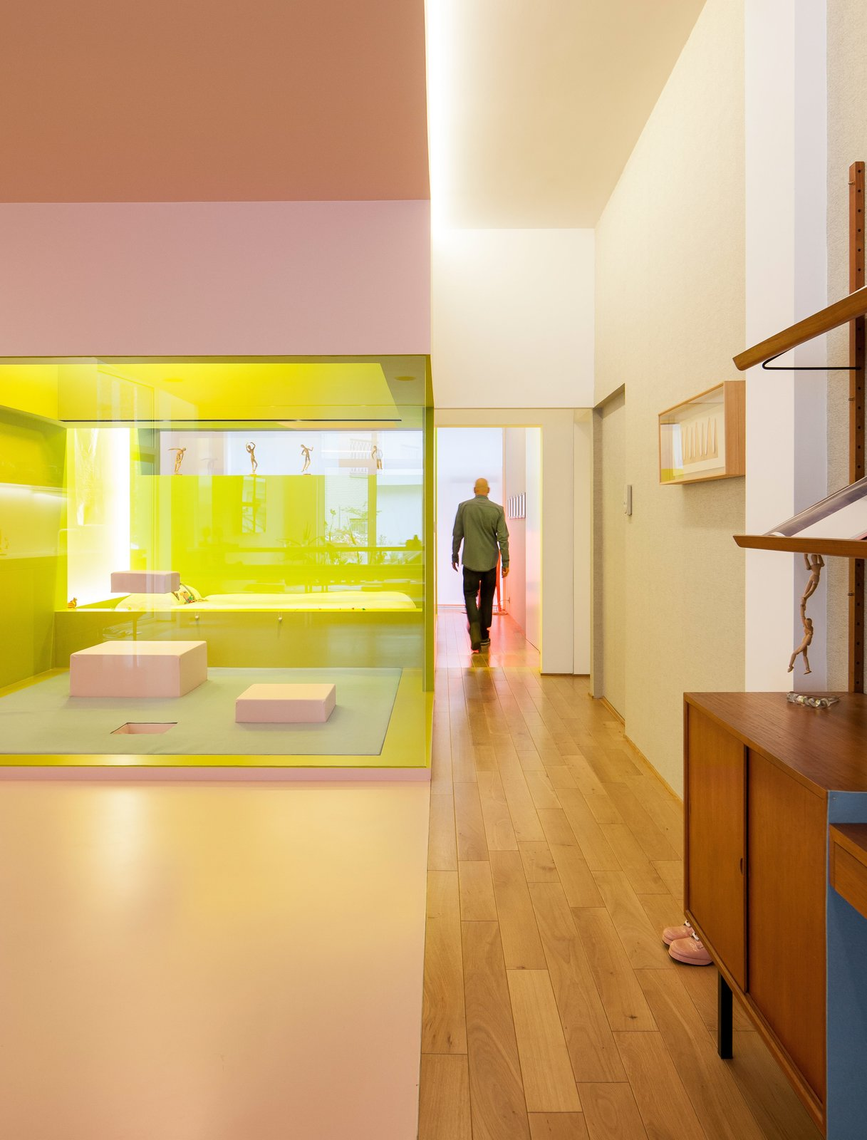 Hallway and Light Hardwood Floor In the upstairs apartment, glass partitions keep the elongated loft open and spacious, while lighting is placed against brightly colored walls to create a cool, atmospheric glow.  Photo 4 of 12 in A Creative Dreamworld Complete With Neon Rooms and a Tropical Garden