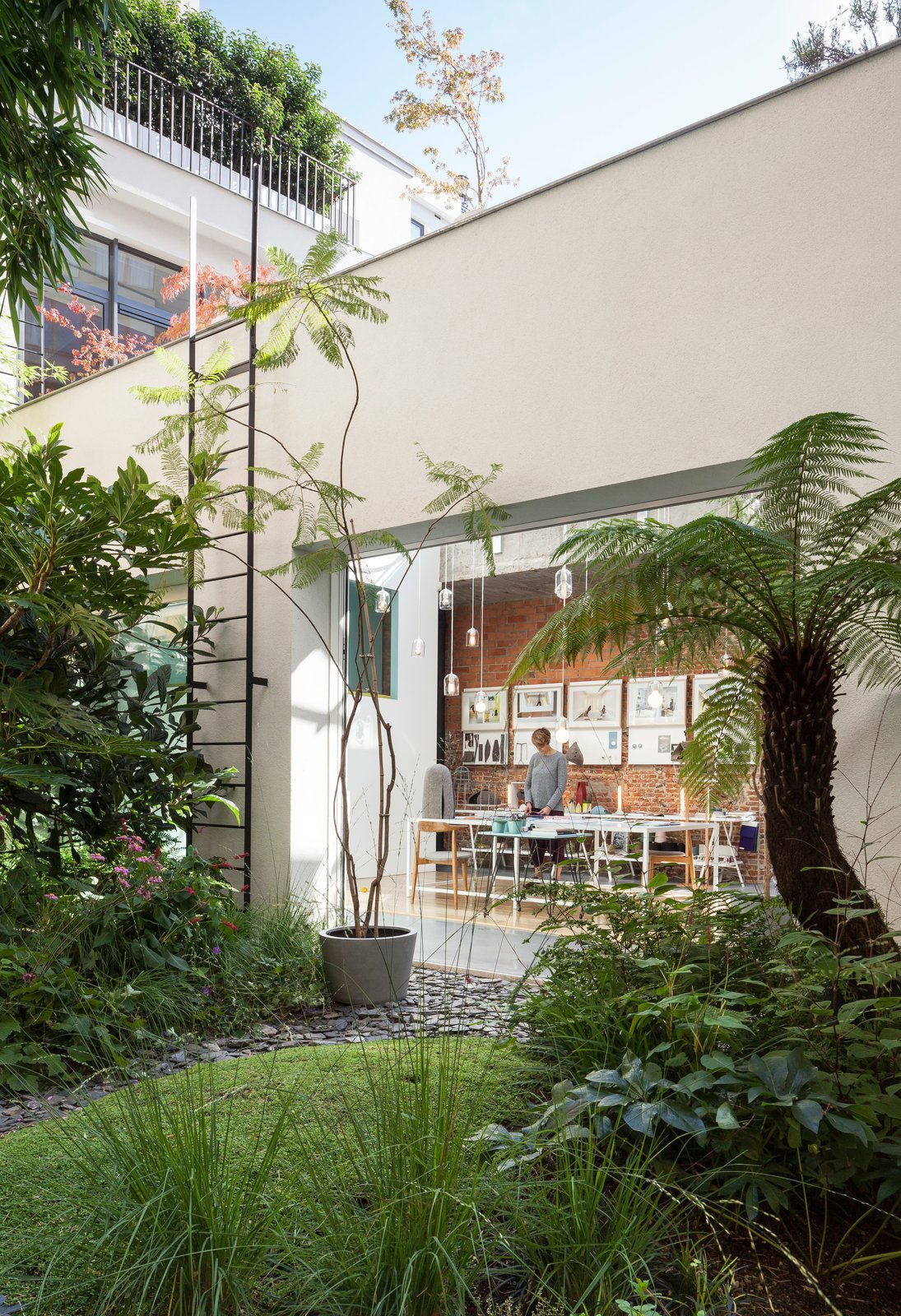 Outdoor, Grass, and Back Yard She also designed the table, surrounded by vintage Wishbone chairs by Hans Wegner, in her studio.  Photo 6 of 12 in A Creative Dreamworld Complete With Neon Rooms and a Tropical Garden