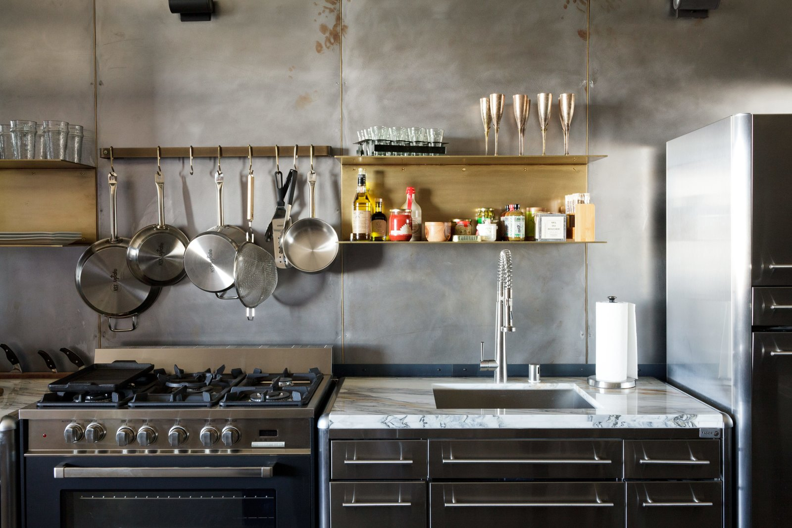 Kitchen, Range, and Undermount Sink Floating brass shelves fabricated by local sculptor Gilad Ben-Artzi contrast the steel wall.  Photo 4 of 6 in Steel and Brass Cover Nearly Every Surface of this Industrial L.A. Kitchen