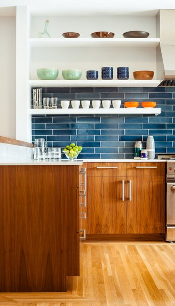 The residents have a particularly strong sense of color and love to cook with their son, so no-fuss finishes likes these blue tiles from Heath Ceramics were an ideal choice. The tiles combine with colorful tableware and custom walnut cabinetry to make a vibrant interior.