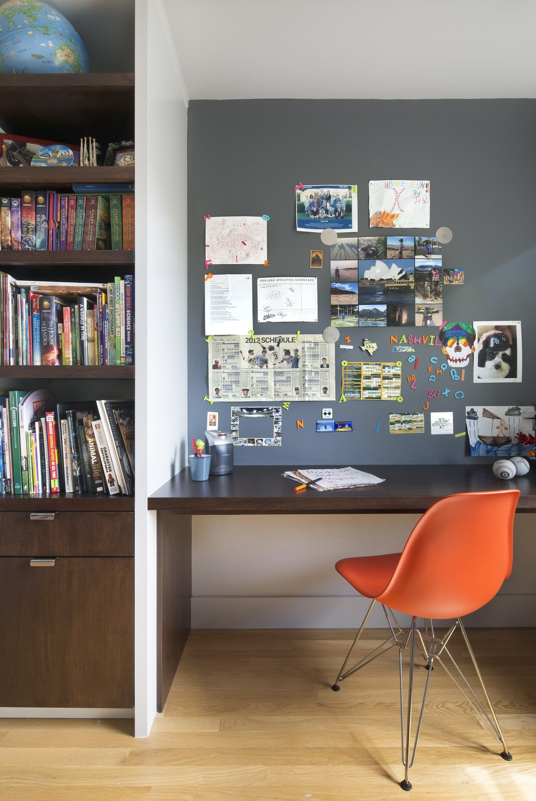 Office, Desk, Chair, and Bookcase Upstairs, their son's bedroom features a built-in walnut bookshelf and desk. Smart details—like the magnetic paint in lieu of a bulletin board—help keep the space tidy. The chair is an Eames Molded Fiberglass Side Chair.  Photo 6 of 11 in 10 Essential Tips For Creating a Hardworking Home Office from A Fresh Kitchen Update for the Family That Cooks Together