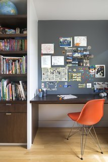 10 Essential Tips For Creating a Hardworking Home Office - Photo 5 of 10 - Upstairs, their son's bedroom features a built-in walnut bookshelf and desk. Smart details—like the magnetic paint in lieu of a bulletin board—help keep the space tidy. The chair is an Eames Molded Fiberglass Side Chair.