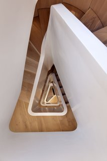 FORMstudio designed an acrylic balustrade that winds up the 1,647-square-foot home's five levels. The flooring throughout is white oak. The staircase is about 46 feet tall from top to bottom.