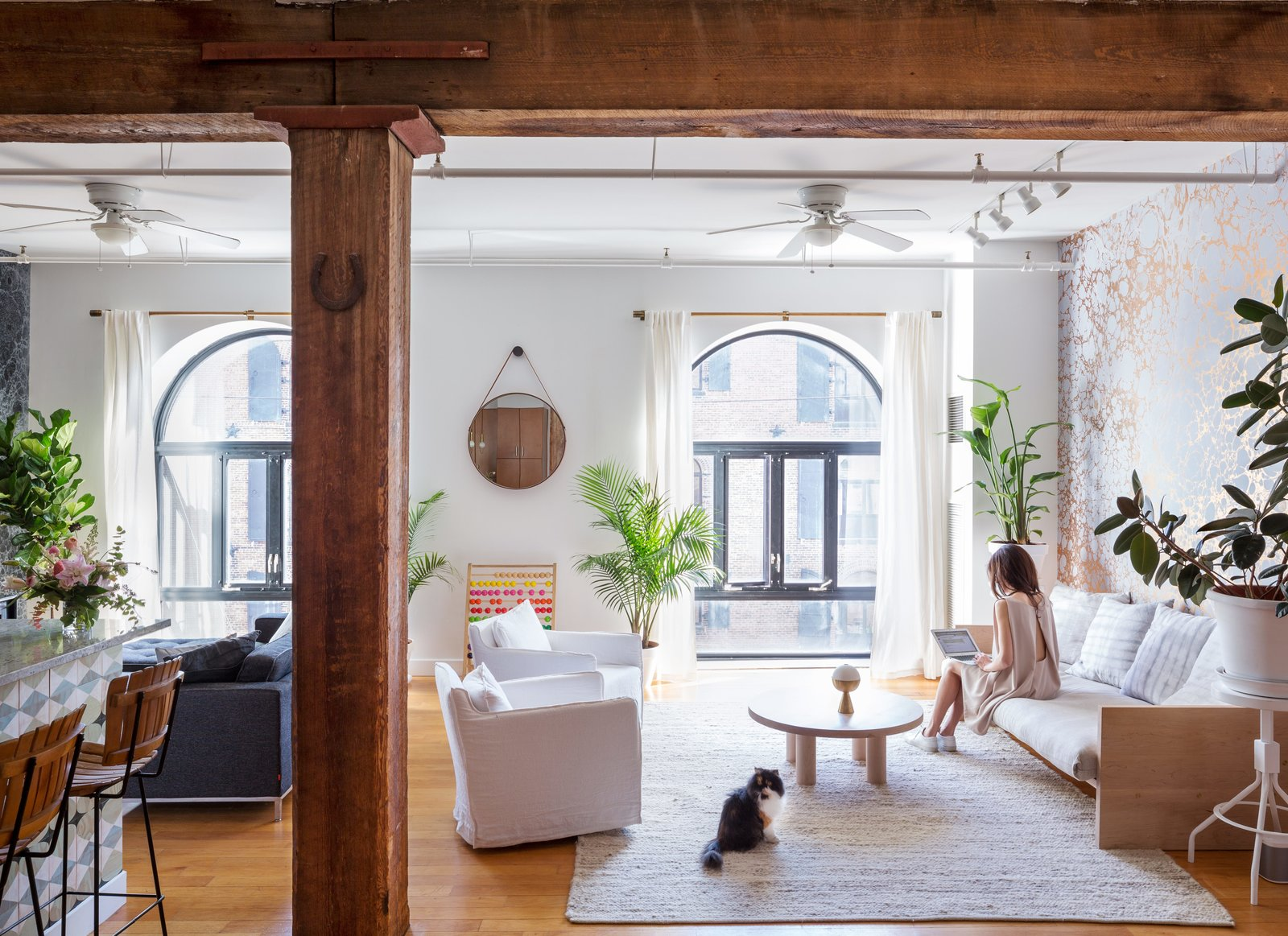 Exposed structural beams are a historic nod to the loft's previous life as a 19th-century warehouse and shipping dock. For the Copes, inspiration for creative projects never draws far from home; they named Calico after their cat, Irie. Tagged: Living Room, Sofa, Chair, Stools, Ceiling Lighting, Track Lighting, Coffee Tables, Light Hardwood Floor, and Rug Floor.  Photo 18 of 21 in 21 Cats Living in the Modern World from Marble Madness