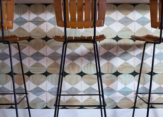 In the kitchen, the couple have applied a series of square plywood tiles by Moonish at the bar counter. Forming a graphic, mosaic-like effect, the geometric designs can be mounted magnetically, in an easy-to-install system that invites reconfiguration and play—for adults and kids alike.