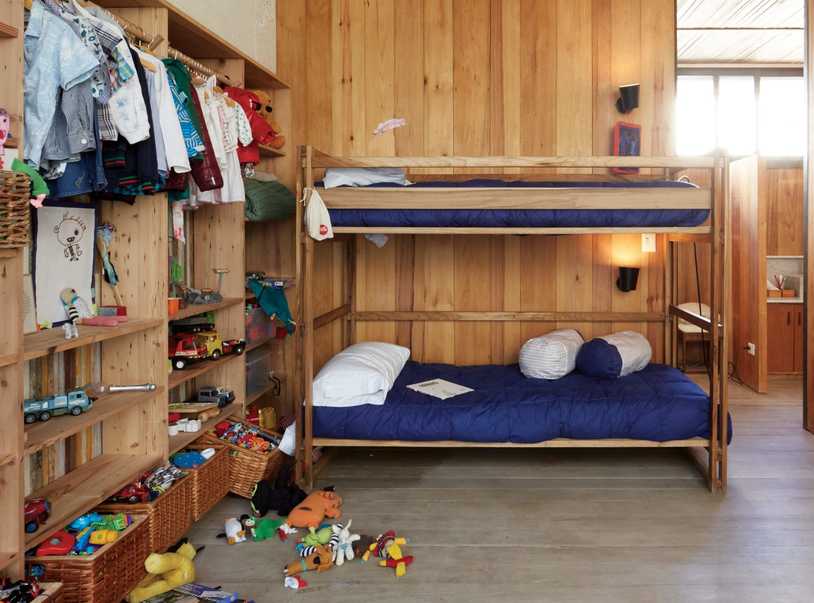 Kids Room, Bedroom Room Type, Bed, Bunks, Pre-Teen Age, Shelves, Light Hardwood Floor, Boy Gender, and Toddler Age The children's bedroom features NET bunk beds and storage baskets from Mono, the design shop of Sticotti's wife, Mercedes Hernáez.  Photo 5 of 10 in One-of-a-Kind Furniture Fills This Delightfully Serene Buenos Aires Home