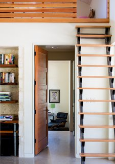 A custom steel and red oak ship ladder in the main living area is another space-saving solution. The door is Douglas fir and the shelving is mesquite wood; an Eames lounge chair can be seen in the master bedroom.