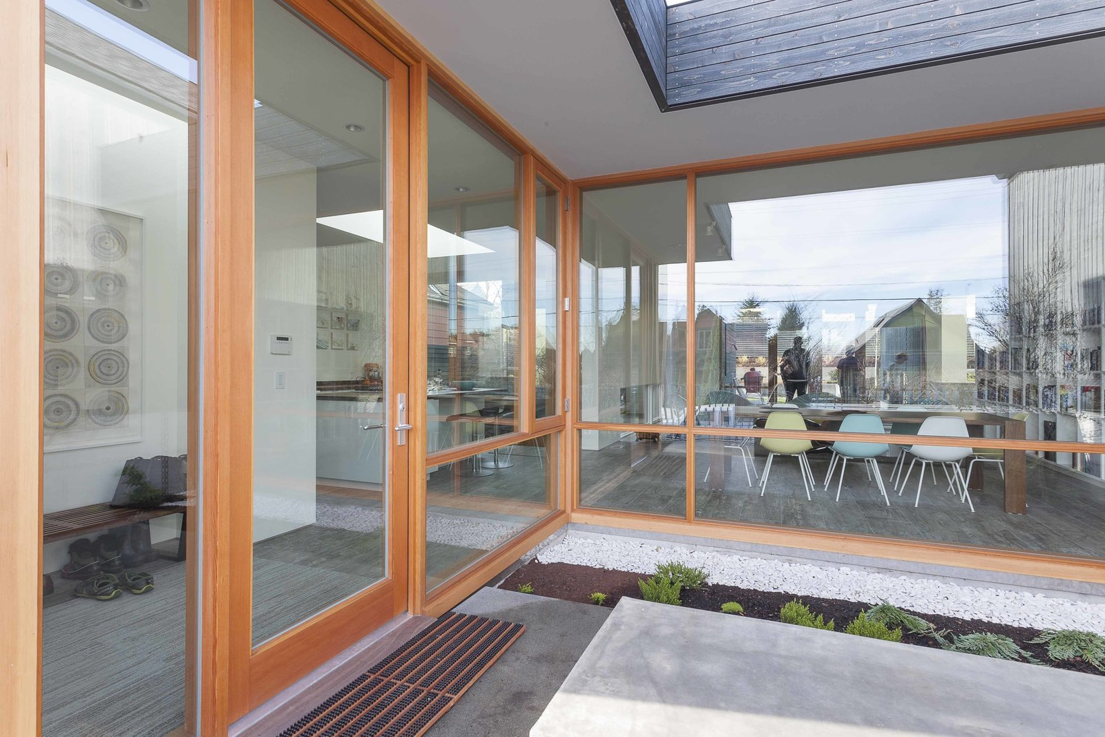 """The front exterior entryway features expansive windows and door by Quantum, which lead into the dining and living area of the main floor. """"[Pulling] as much natural light into the interior as possible"""" was one of the clients' biggest requests, says architect Mike Mora of Heliotrope.  Central District Residence by Sarah Akkoush"""
