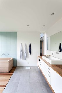 The owners were passionately involved in every aspect of the design, and pushed the team to make choices they normally might not have, including using Western red cedar for the master bathroom countertop. The spa-like space features a soaking tub, tile from Statements Urban, an MTI sink, a custom mirror, and a Vola faucet.