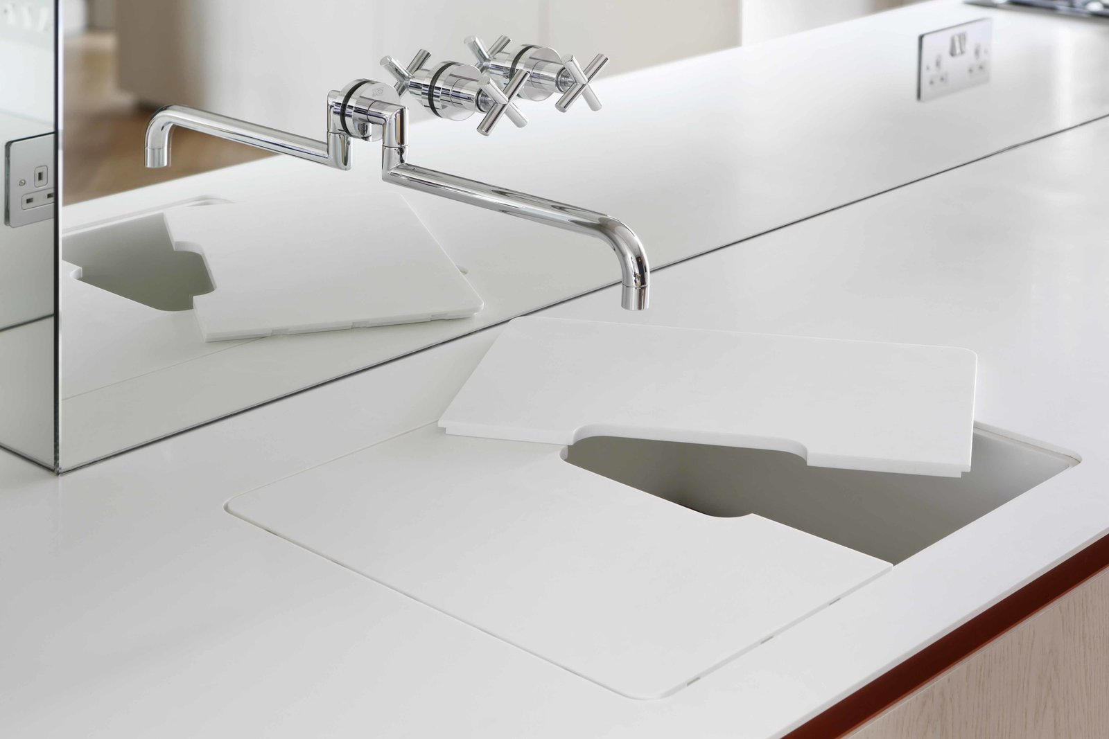 A Dornbracht tap sits above a custom-built glacier white Corian countertop and sink. The sink is covered by a removable cutting board that can be kept in place for an added work surface, or removed for dedicated sink use. The cutout in the center allows water from the tap to flow straight through to the custom Corian drainer.