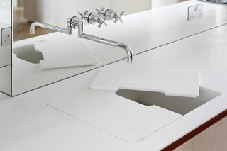In a London flat designed by MWAI, the design team benefited from a collaborative relationship with their client, one of the owners of UK-based millwork and joinery company INTERIOR-iD, who produced many of the custom elements. Here, a custom-built Corian countertop and sink merge when the sink basin is covered by a removable cutting board that can be kept in place for an added work surface, or removed for dedicated sink use. The cutout in the center allows water from the tap to flow straight through to the custom Corian drainer.