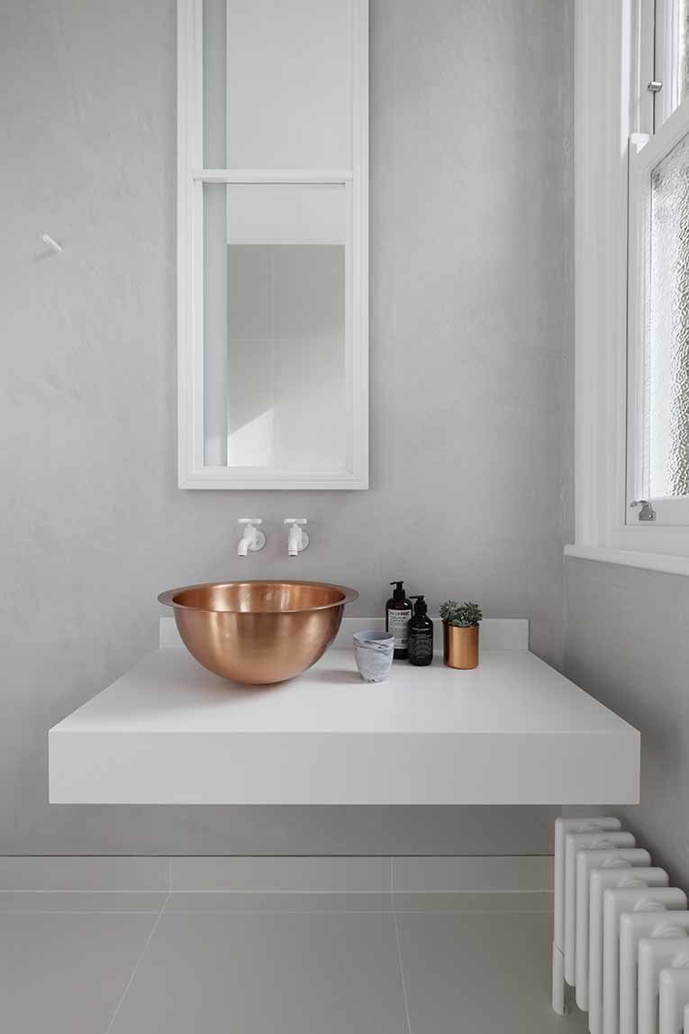 Bath Room and Vessel Sink Metal details in the home transition to gradually darker tones as the spaces become increasingly private. In the guest bathroom, a solid brass bowl sink rests on top of a custom Corian base. White Dornbracht wall-mounted faucets sit below a custom mirror cabinet. In the bathroom and throughout the home, interior accents by Gunter & Co make elegant finishing touches.  Photo 8 of 10 in 10 Ideas For the Minimalist Bathroom of Your Dreams from Brass Is Everywhere at this Classical-Meets-Modern Flat in London