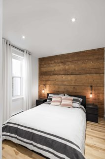 In a project in Quebec, Canada, a 1924 building was renovated by Bourgeois Lechasseur Architects. The renovation sought to modernize the apartment while preserving the historical elements—in particular, reusing wooden boards that were salvaged during demolition. The unfinished boards act as a rustic, earthy accent wall and headboard, while the surrounding white walls and crisp bed linens keep the room contemporary.