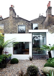 The rear of the house features Victorian brick, a modern extension, and Velfac windows. Landscape designer Matthew Wright was inspired by the art of Henri Rousseau when choosing plants to set amid the garden's Dorset pebbles.