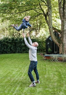 We Can't Get Enough of This German Apartment's Sleek Matte-Black Kitchen - Photo 6 of 11 - Fabian plays with Morten in the yard, which features a spacious lawn and a greenhouse.