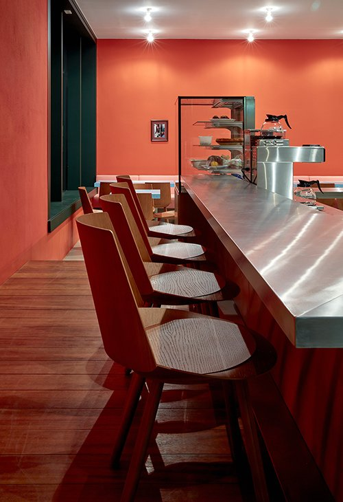 The restaurant features a special edition of the Houdini chair by Stefan Diez for e15 which tuck underneath a stainless-steel bar at the open kitchen.  Photo 3 of 5 in New Restaurant Brings Palm Springs Modernism and NYC Deli Style to...Berlin?