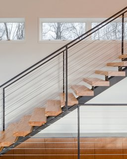 """The clients desired a maintenance-free, year-round home using the ultimate in 'green' building methodologies,"" Mulvena says. The staircase is an example of the construction's mindset: it is made from the leftover laminated veneer lumber used on the roof."
