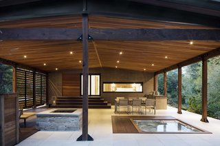 The open terrace is fitted with recessed lighting by Foscarini and a StoneTile floor. It houses an outdoor kitchen and dining area, as well as a fireplace and a spa. Inside, it connects to a gym and sauna in the basement.