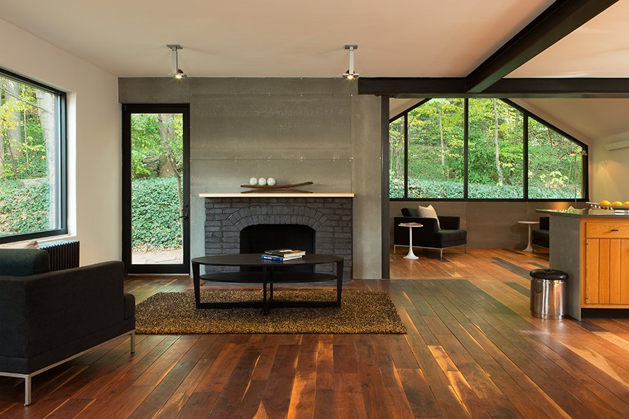 Living Room, Medium Hardwood Floor, Wood Burning Fireplace, and Standard Layout Fireplace Industrial finishes include Viroc cement fiber panels over the fireplace.  Photo 5 of 5 in Steel Preserve