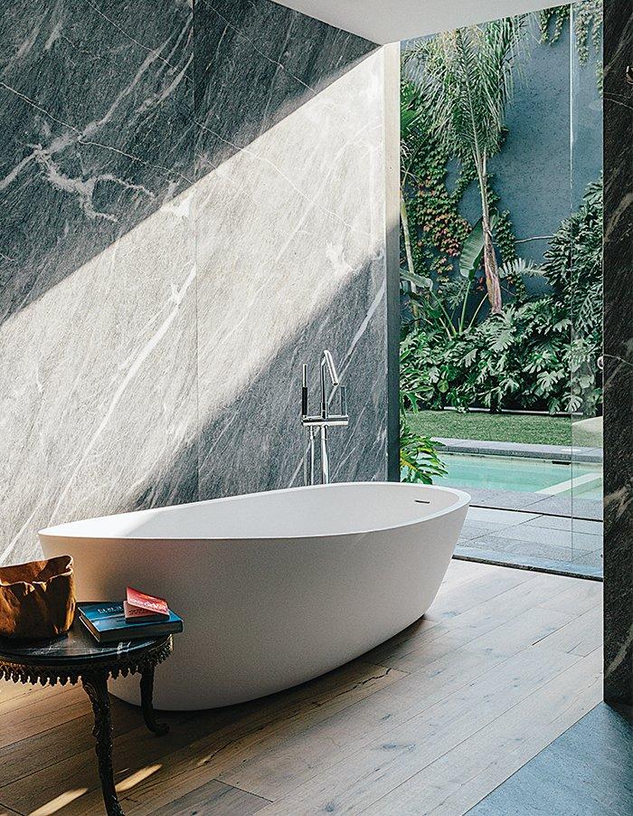 Bath Room, Freestanding Tub, Marble Wall, and Medium Hardwood Floor #bath #spa #bath&spa #modern #interior #interiordesign #bathroom #pool #indooroutdoor #woodfloor #courtyard #mexicocity #almondtub #porcelanosa #hansgrohe   Photo by Grant Harder    Photo 13 of 22 in Bath & Spa Intrigue