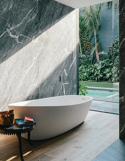 "The drama of this green marble remains soothing and calming as it gives floor-to-ceiling views of a lush garden beyond. In fact, the bathroom in this home in Mexico City is an extension of the home, which, as the designer and owner described it, was intended to be ""a retreat, a kind of a temple."""